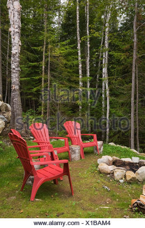 Red Plastic Garden Chairs Around Rock Fire Pit In Backyard Of Cottage Style  Log Home