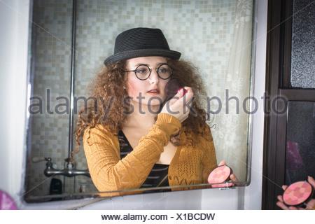 Woman applying makeup in mirror - Stock Photo