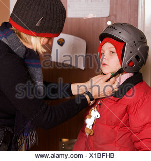 Mother helping child putting on a helmet, Sweden. - Stock Photo