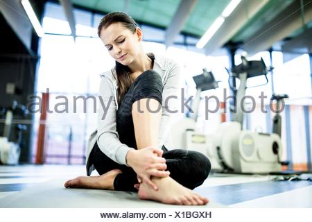 PROPERTY RELEASED. MODEL RELEASED. Young woman massaging ankle while having ankle pain in gym. - Stock Photo