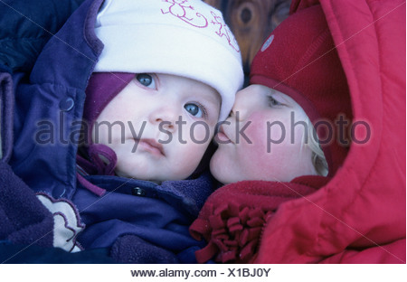 Girl kissing her little brother on the cheek - Stock Photo