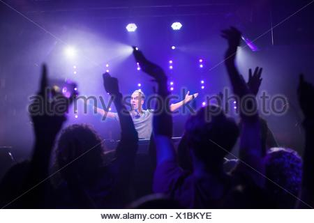 Group of friends watching DJ in club - Stock Photo