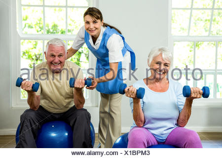 Portrait of smiling nurse assisting senior man and woman - Stock Photo