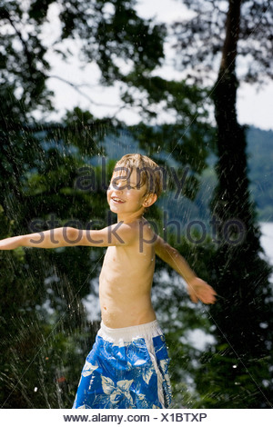 A boy playing in spraying water - Stock Photo