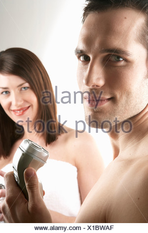 Young man shaving his face with woman in background - Stock Photo