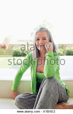 Woman sitting outdoors with head in hands - Stock Photo