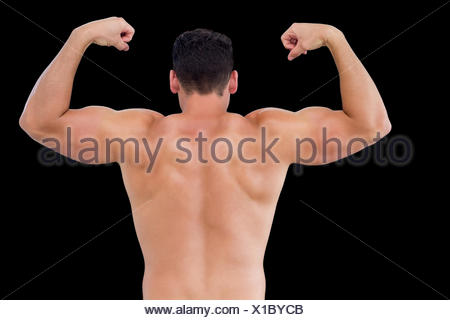 Rear view of shirtless muscular man flexing muscles - Stock Photo