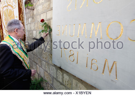 Freemason placing a rose on the Mur des Federes in the Pere Lachaise cemetery (commemorating the victims of the 1871 Paris Commu - Stock Photo