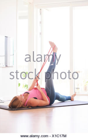 Pregnant young woman doing exercise in living room raising her leg - Stock Photo
