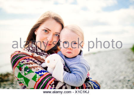 Portrait of mother holding son while standing on beach - Stock Photo