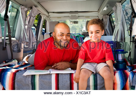 Father and son sitting in trunk of car with camping gear - Stock Photo