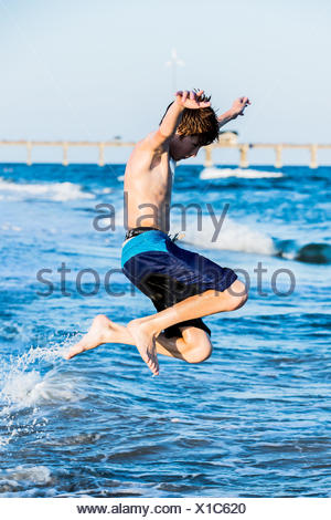 Redhead boy on the beach jumping in the surf - Stock Photo
