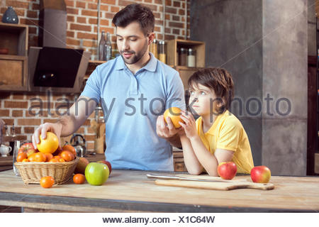 Father and son selecting fruits from basket at kitchen table - Stock Photo
