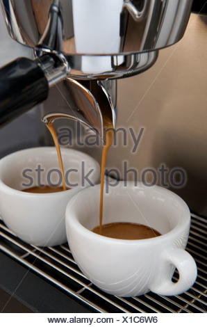 Professional preparation of espresso with an espresso machine: the espresso is flowing out of the filter into the espresso cups - Stock Photo
