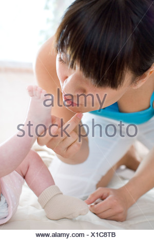mother kissing baby's feet - Stock Photo