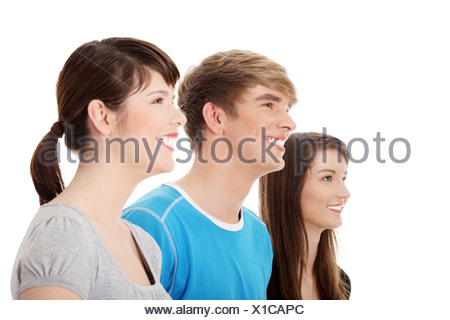 Three young happy friends. Two girls one boy smiling and looking left. Focus on male. Isolated on white background. - Stock Photo