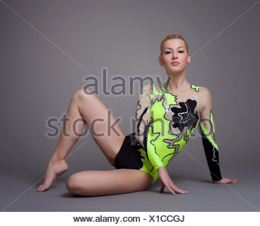 Young woman in gymnast suit posing on grey - Stock Photo