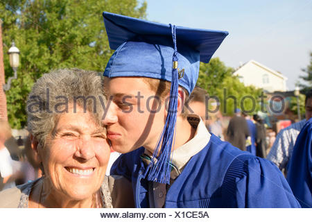Teenage boy kissing grandmother at graduation ceremony - Stock Photo