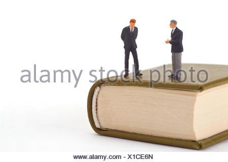 Stehende Miniaturfiguren auf  Buch freigestellt auf weissem Hintergrund - Stock Photo
