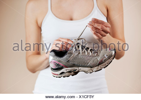 A young woman undoing the laces of a training shoe - Stock Photo