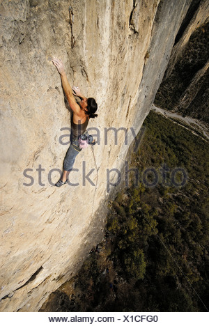 A rock climber ascends a steep rock face in Mexico. - Stock Photo