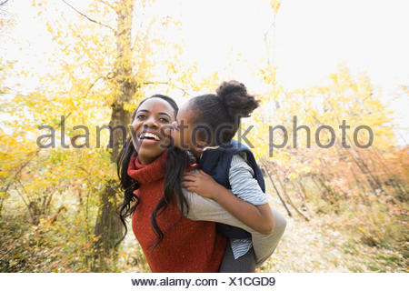Daughter kissing mother in autumn woods - Stock Photo