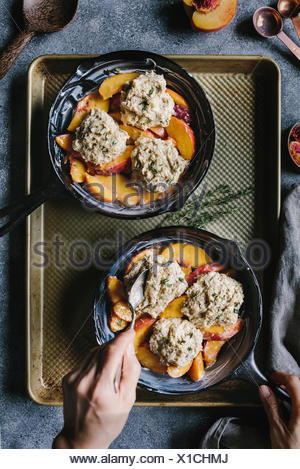 A woman is placing the last biscuit on top of peaches. - Stock Photo