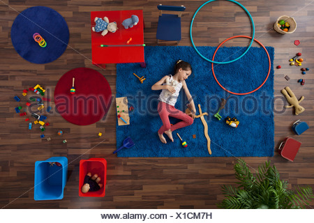 A little girl lying on a rug with toys, overhead view - Stock Photo