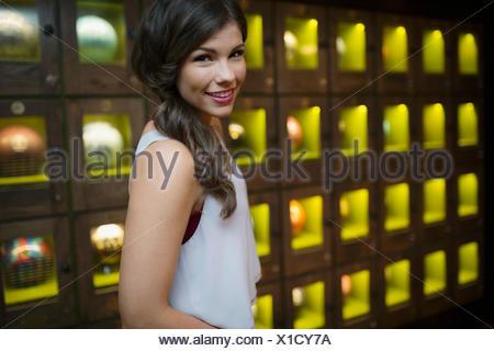 Portrait smiling young woman near bowling ball lockers - Stock Photo