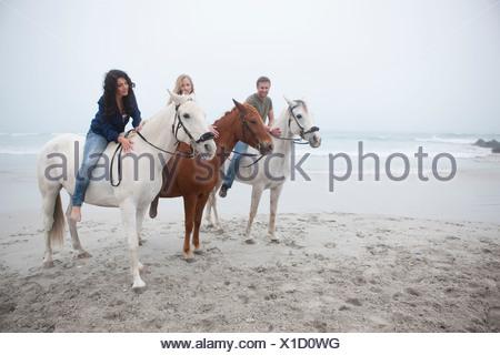People riding horse on beach - Stock Photo
