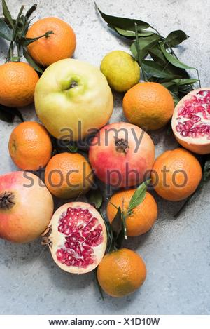 Overhead view of colourful fruits and halved pomegranate - Stock Photo