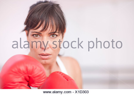 Portrait of mid adult woman in boxing gloves - Stock Photo