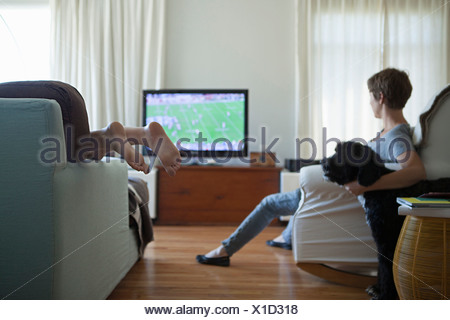 Mother and daughter watching television with dog - Stock Photo