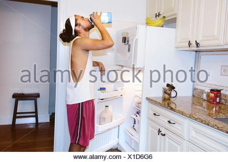 Young man standing next to open fridge, drinking milk from carton - Stock Photo