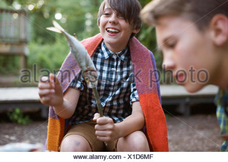 Young boy holding stick with fish on ready to barbecue - Stock Photo