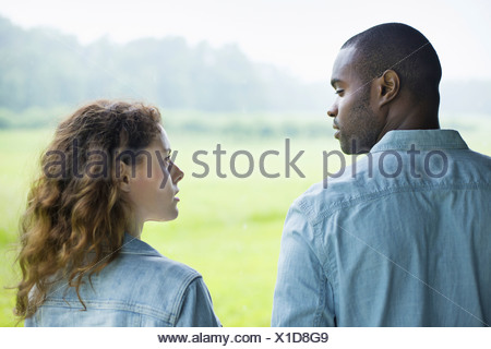 A young man and woman a couple  side by side. Looking at each or. - Stock Photo