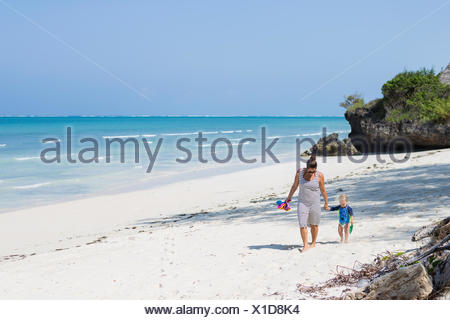Mother and son walking on Diani Beach, Kenya - Stock Photo