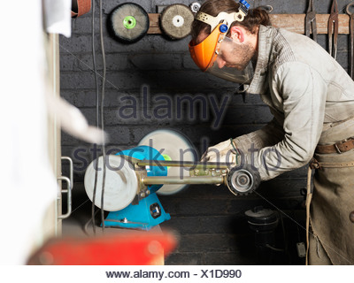 Blacksmith working on machine in workshop - Stock Photo