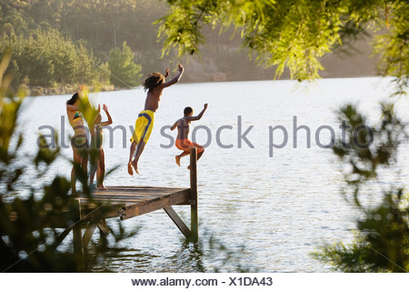 Father and son 8 10 in swimwear jumping off jetty into lake mother and daughter 7 9 cheering rear view - Stock Photo