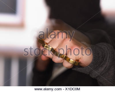 Young man showing fist with brass knuckles - Stock Photo
