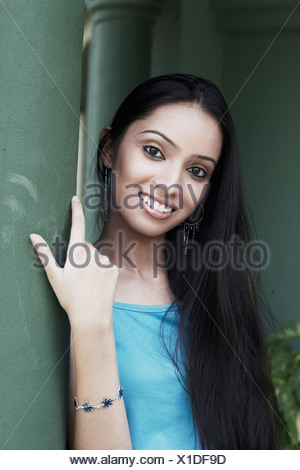 Portrait of a teenage girl leaning against a column smiling - Stock Photo