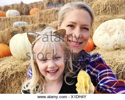 Close-Up Of Happy Mother And Daughter Against Pumpkins - Stock Photo
