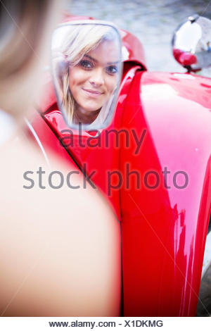 Young woman looking into rear-view mirror of car - Stock Photo