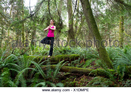 Mature woman performing tree pose in forest - Stock Photo