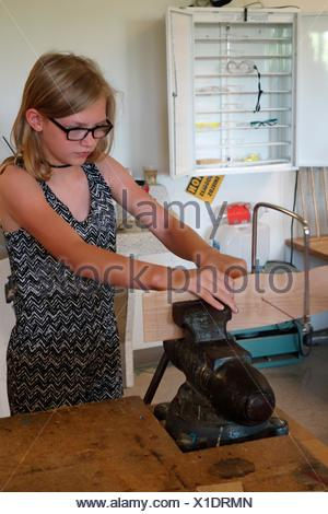 6th Grade Girl Using Coping Saw With Vice in Technology Class, Wellsville, New York, USA. - Stock Photo