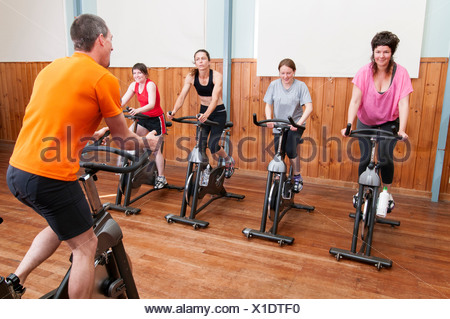 Male instructor and female spinning class - Stock Photo