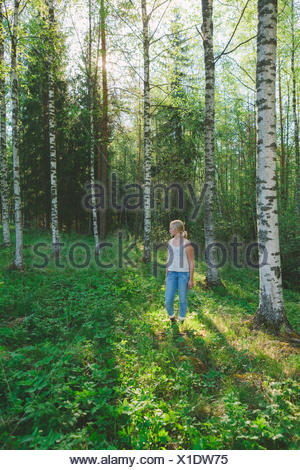 Finland, Mellersta Finland, Jyvaskyla, Saakoski, Woman standing in forest glade - Stock Photo