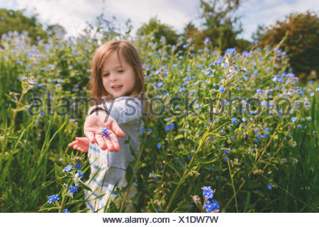 Girl holding a flower in the palm of her hand - Stock Photo