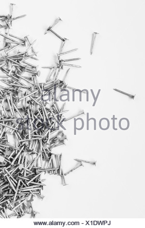 Galvanized nails spread out on white background - Stock Photo