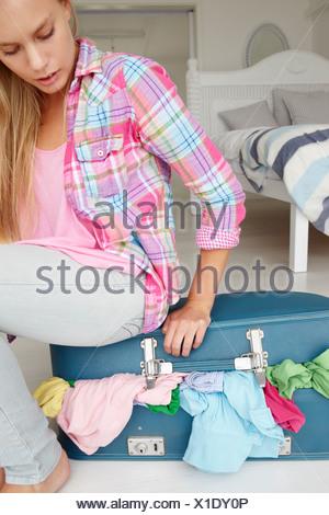 Teenage girl struggling to close suitcase
